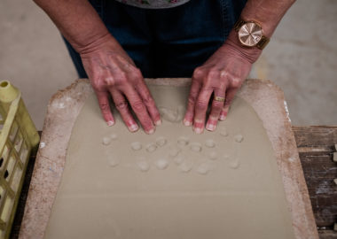 A pair of hands are pressing into a soft slab of clay, leaving their finger's imprints.