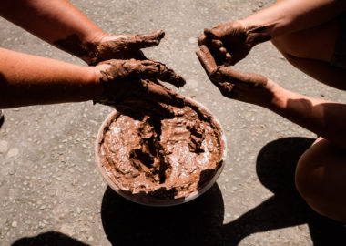 Two people are crouched over a bucket, their hands are covered in clay.