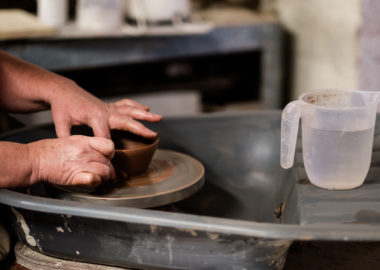 A person throws a bowl on the wheel with red clay.