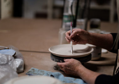 An artist uses a paintbrush on a raw plate.