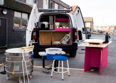 The BCB van surrounded by ceramic equipment including a wheel and various tools.