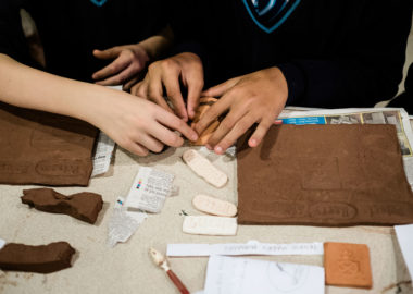 Children stamp the surface of red clay and make marks with tools.