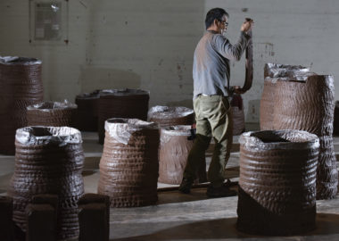 Artist handbuilds huge cylinders with coils of clay.