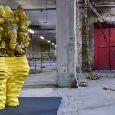 A tall ceramic sculpture with a yellow glaze standing in front of ceramic chains which are hanging from the ceiling.