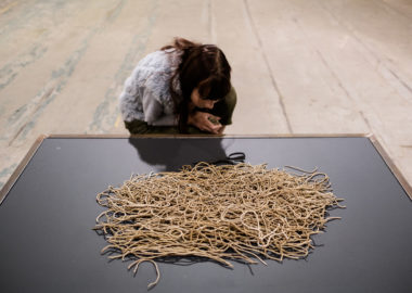 A visitor crouches down to see ceramic thread displayed on a plinth.