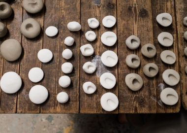 Rows of white and terracotta ceramic pebbles are lined up on a wooden table, varying in size.