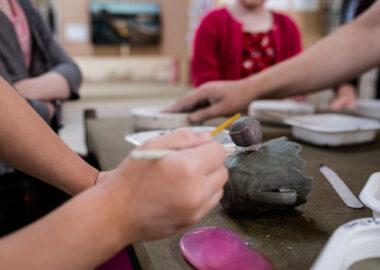 A festival visitor paints slip (liquid clay) onto a teacup.