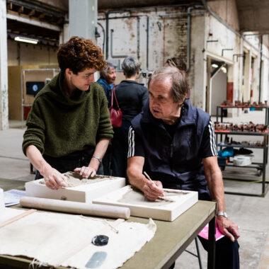 Sarah Fraser helps a festival visitor press moulding ceramics.