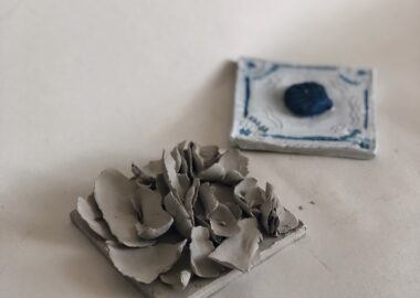 Two clay tiles are displayed on cream paper. One has handmade rose petals attached and the other is painted white with a blue shell attached in the centre.