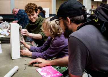 Artist Sarah Fraser demonstrates a press moulding technique using raw clay and a white ceramic mould to a visitor. The photo was taken during BCB's 2019 festival.