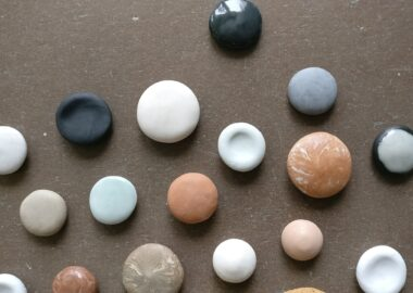 This images shows a collection of pebbles made from different types of clay. They vary in size and colour from red, white and grey to others which are glazed blue.