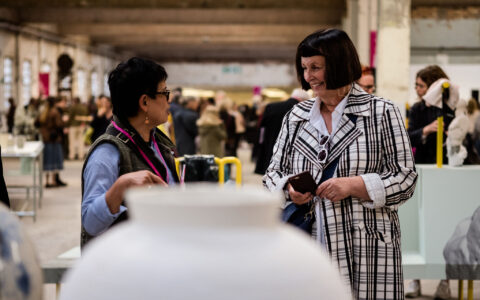 A large ceramic vessel by Adam Buick sits in the foreground in front of two women visiting British Ceramics Biennial 2019.