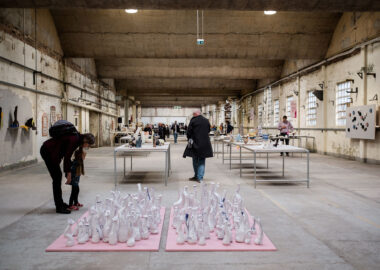 Visitors to British Ceramics Biennial 2019 are looking at ceramics exhibited on tables and the floor. The exhibition is in the centre of Spode China Hall in Stoke.