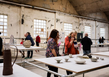 Visitors looking at ceramics displayed on large plinths in the middle of Spode China Hall in Stoke-on-Trent.