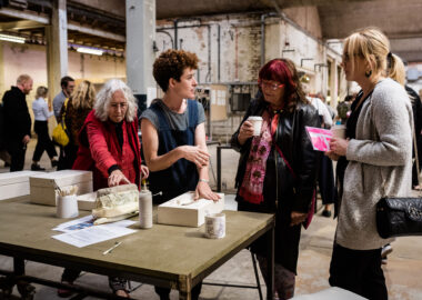 Artist Sarah Fraser is having a conversation with a visitor to British Ceramics Biennial 2019. She is causally leaning on a white ceramic mould.