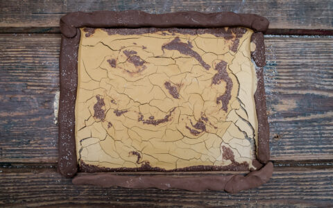 A slab of red clay with yellow slip cracking on top.