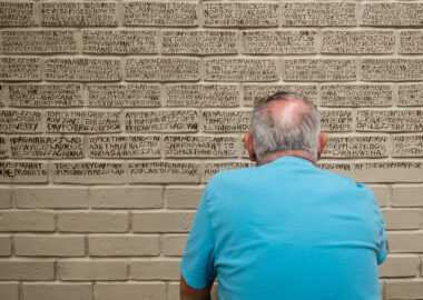 An artist sits in front a large clay wall with his back to the camera, writing poetry into the clay.