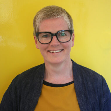 Clare Wood stands against a yellow background wearing black glasses, a black cardigan and mustard top.