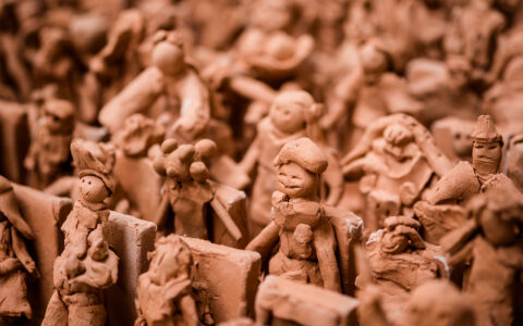 Terracotta clay figurines displayed in rows.