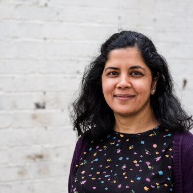 Associate Artist Zeba Imam is smiling at the camera, standing in front of a white brick wall.
