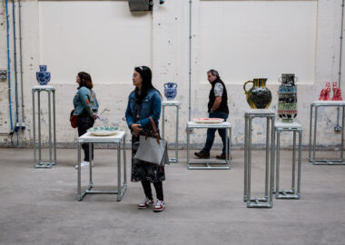 Festival visitors stand among ceramics displayed on plinths at varying heights.