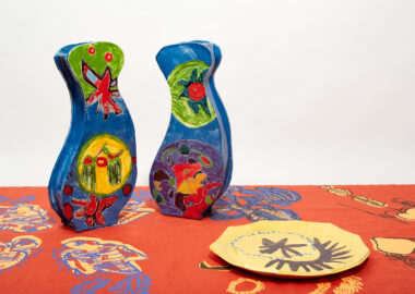 Brightly coloured ceramic sculptures and a yellow plate are exhibited on a pattern tablecloth.
