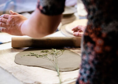A person presses dried flower stems into a slab of grey clay to leave a mark.