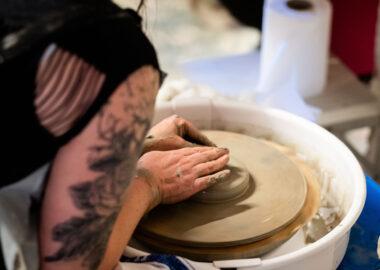A person centres a lump of grey clay of a pottery wheel.