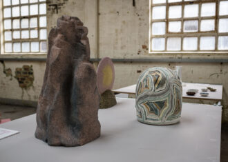 Three ceramic sculptures are displayed on a table, backlit by light in Spode Factory Hall.
