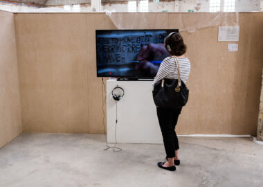 A festival visitor watches a film on a tv screen with a pair of headphones on.