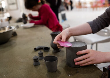 A person smooths the bottom of a pot with a pink plastic kidney tool.