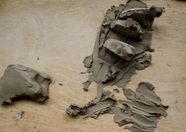 Broken pieces of clay are assembled like a sculpture on a wooden desk.