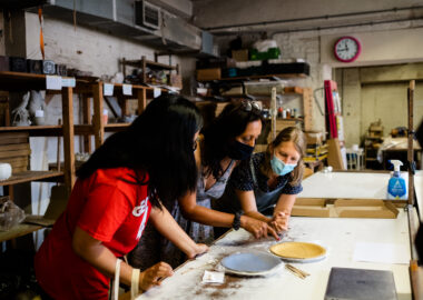 Three people work together to make plates in a ceramics studio.