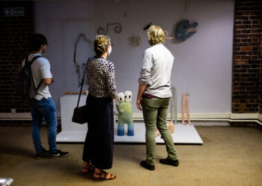 Three festival visitors look at an installation of brightly coloured sculptures displayed on the wall and floor.