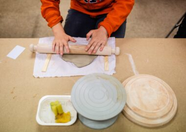 A young person rolls out a slab of clay with a rolling pin.