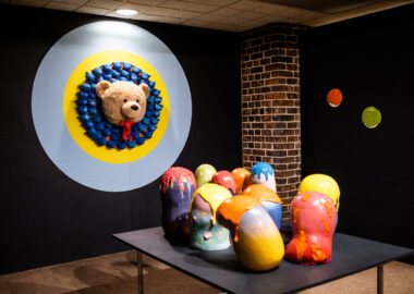A collection of colourful ceramics sculptures are displayed on a black plinth infront a a teddy bear's, wall-mounted head.