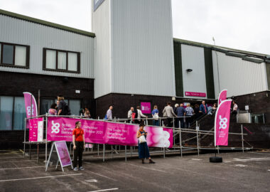 People queue up infront of a grey building, The Goods Yard, to get into BCB 2021 festival.